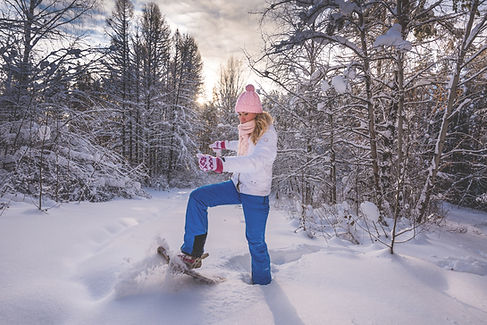 Woman with snowshoes on fluffy snow in f