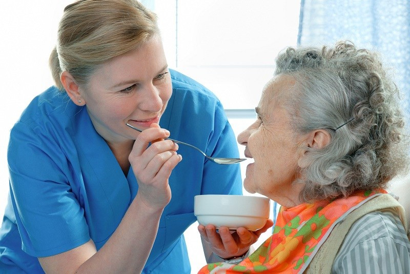 In-home caregiver feeding elderly woman