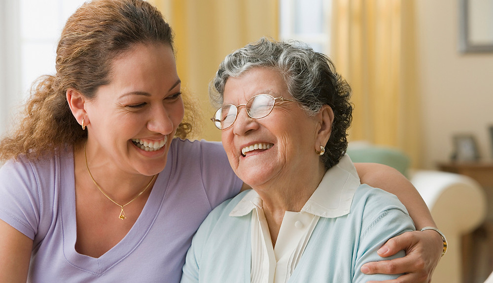 Woman laughing and  shoulder hugging a laughing older woman