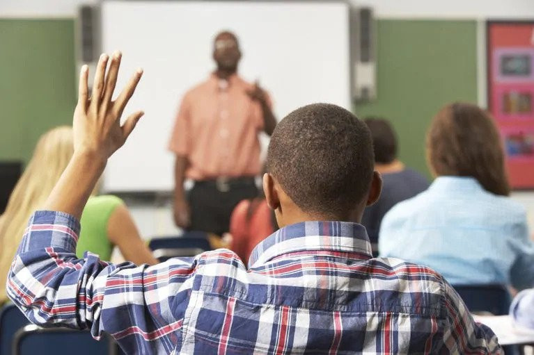 Black student raising hand in class for college readiness
