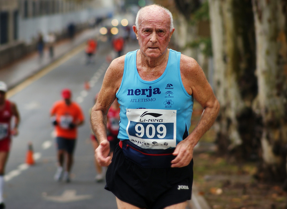 Elderly man running a road race/marathon
