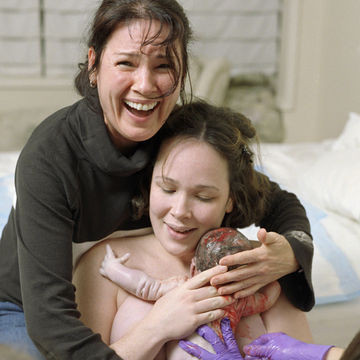 Woman and doula holding newly born baby