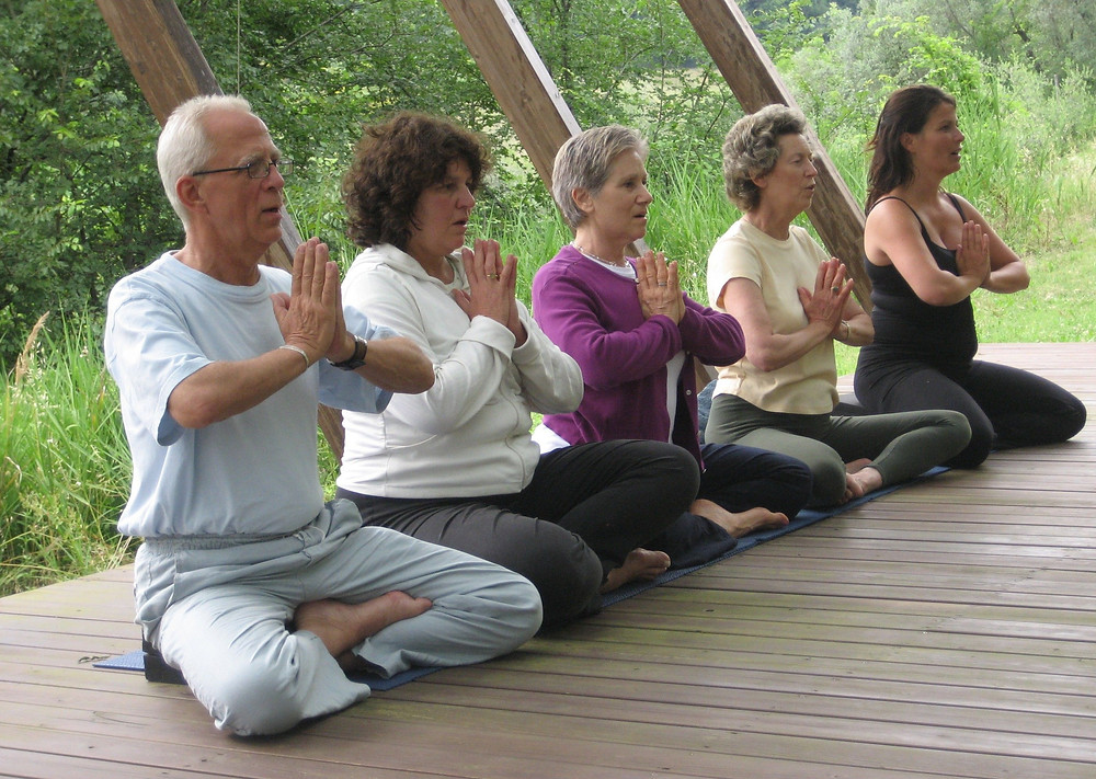 Elderly people meditating on a deck