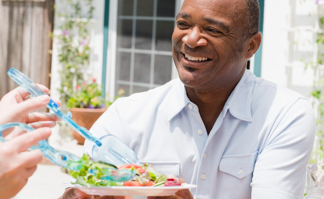 smiling senior black man served salad