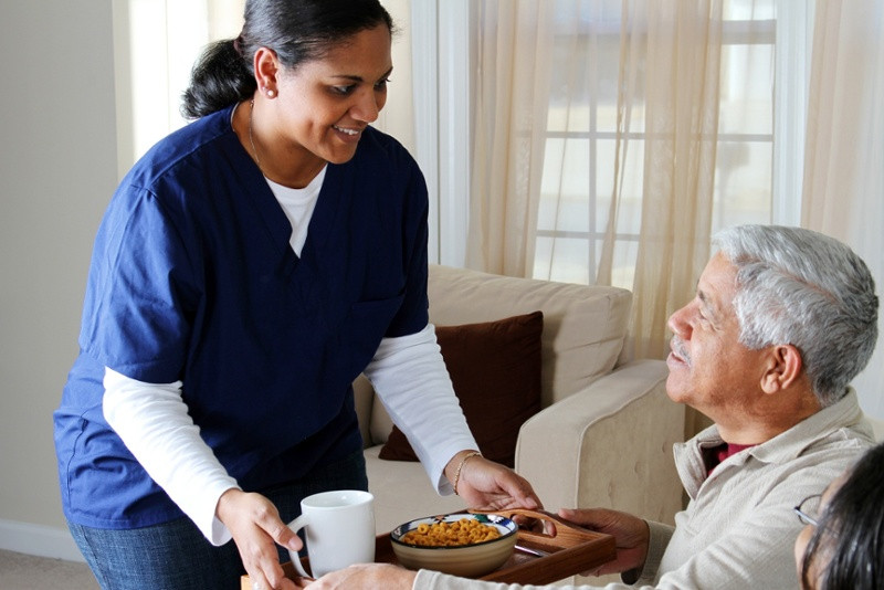 Caregiver serving cereal to senior on a tray