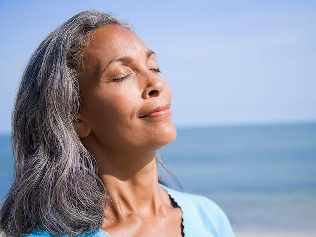 older woman closing eyes basking in sun