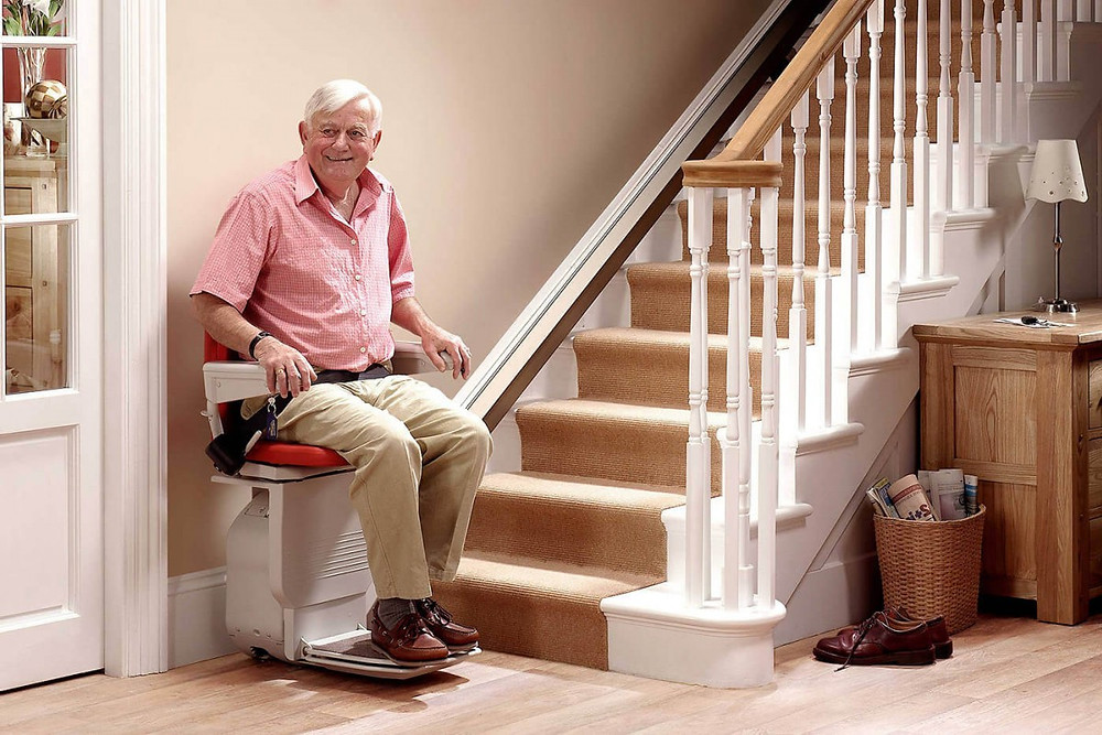 Old man smiling while using stair lift