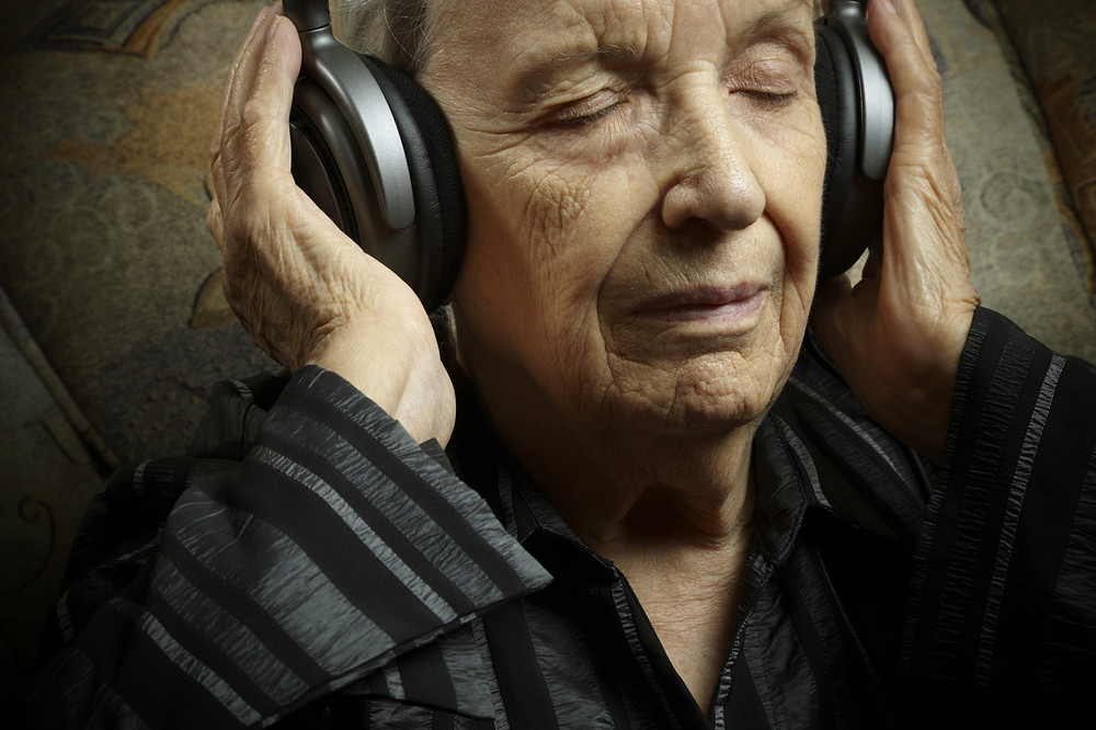 elder woman with dementia listening to music as therapy