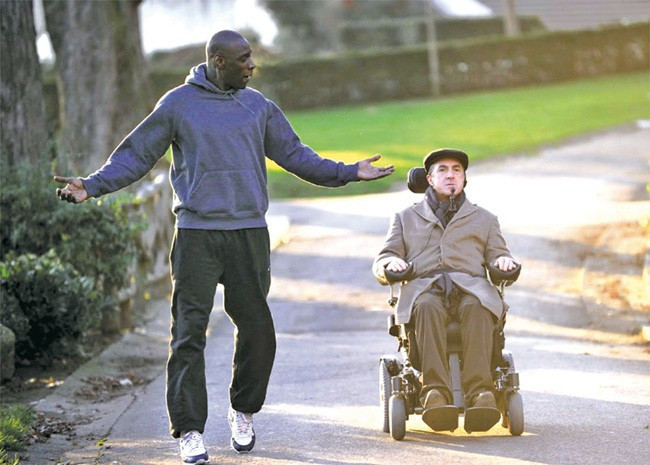 Caregiver walking and talking with  patient in wheelchair from the intouchables movie
