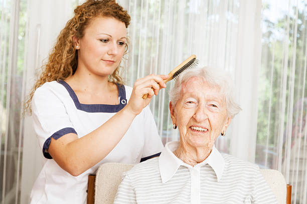 Caregiver brushing senior patient's hair