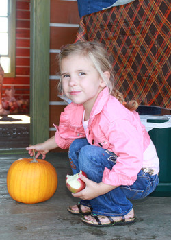 Girl posing with apple and pumpkin