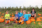 Group of kids sitting on pumpkins in pumpkin patch