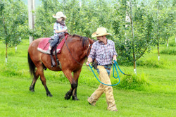 Cowboy leading young child on horse