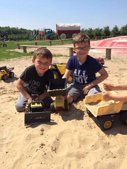 Two boys playing with trucks in sand