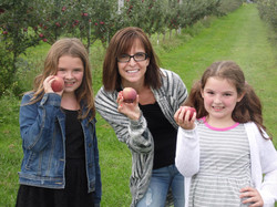 Family holding up apples picked