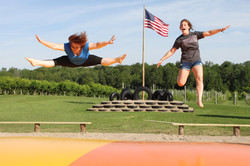 Two girls jumping on bouncy pillow