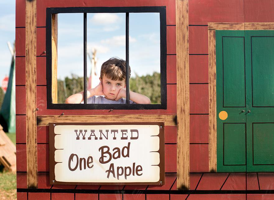 Young boy posing in wanted sign