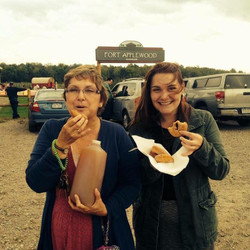 Two women eating apple cider donuts