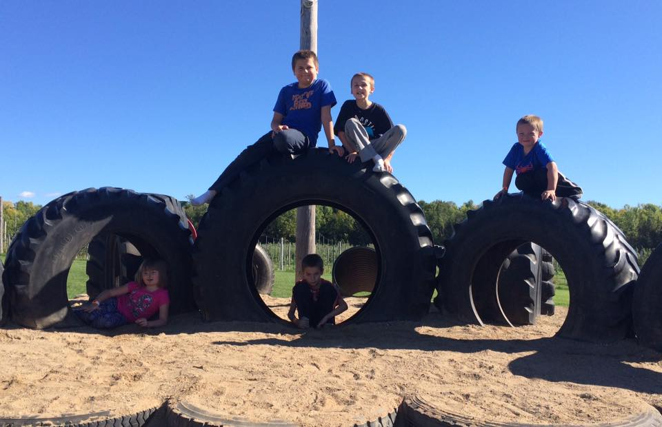 Children sitting on large tires