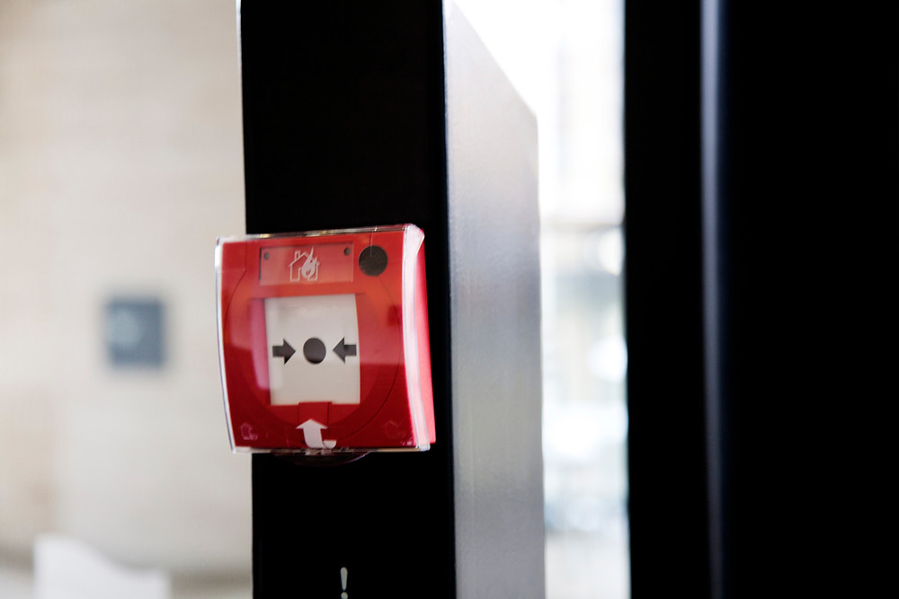 pic of a square shaped device. break rh glass in the centre to set an alarm off to warn of fire