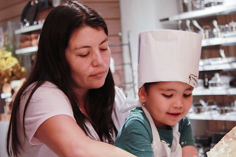 A mother and child making pizza during the pizza class.