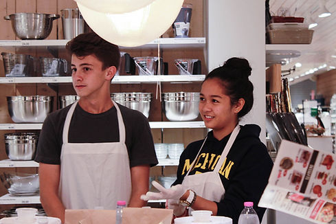 Two teenagers with aprons during a pizza class.