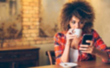 mulher-tomando-cafe-mexendo-celular.jpg