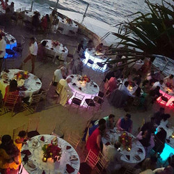 A view of guests mingling & having appetizer on the beach at La Mansion
