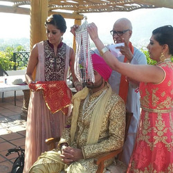 The Groom is getting ready by his sisters for his wedding ceremony.
