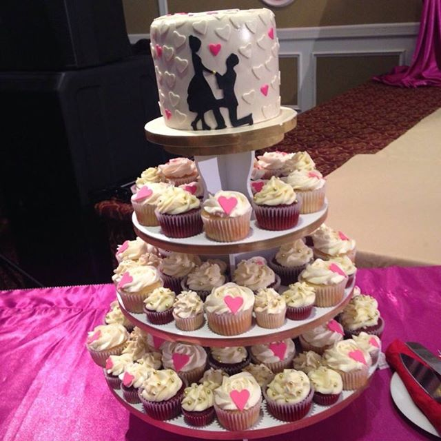 An adorable cake with cupcakes for the wedding reception