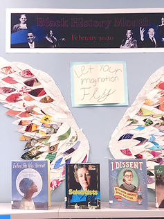 "Library books of historical women in front of large Wings made of library book pages with a poster, ""Let your imagination fly."""