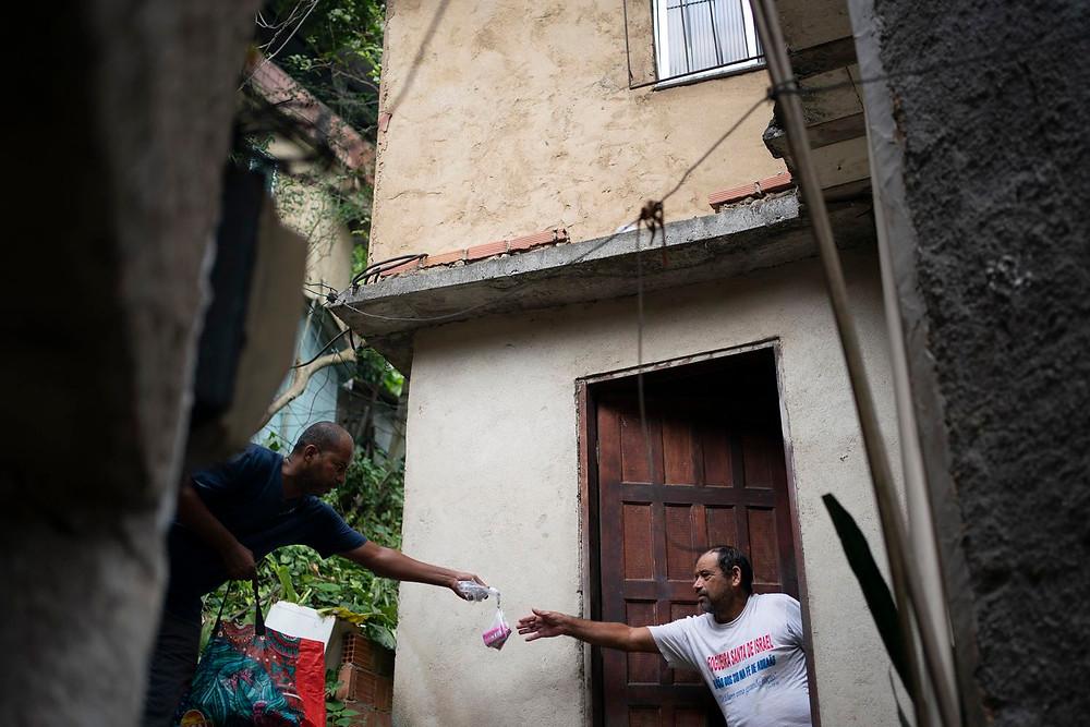 Voluntário entrega sabonete para um morador da favela da Rocinha, Rio de Janeiro, no dia 24 de março. LEO CORREA / AP.