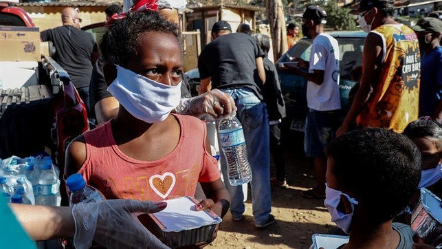 Fotografía fechada el 31 de mayo de 2020 de niños recibiendo una donación de alimentos en la comunidad de Capadócia, en Brasilandia, un barrio en la periferia de la ciudad de São Paulo (Brasil). EFE.