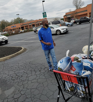 Black man with beard wearing blue short shirt with jeans outside with a black shopping cart full of turkeys in the corner