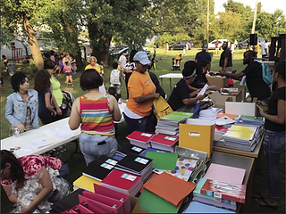 Table of binders and notebooks with many people giving out those items outside with lots of green trees