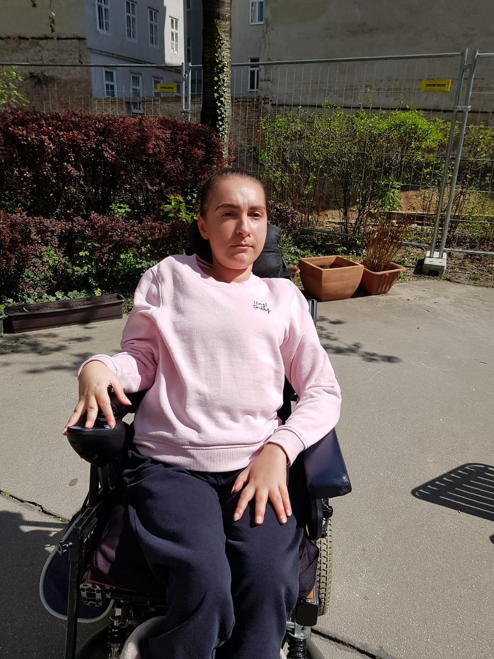 Lidija Ljubic in einem sonnigen Vorhof im Rollstuhl sitzend mit rosa Pullover