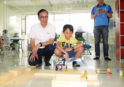 前新北市長朱立倫參訪光點創意樂高機器人創客中心並和孩子參與暑期夏令營機器人及程式設計課程,由記者拍攝朱立倫與學生合影