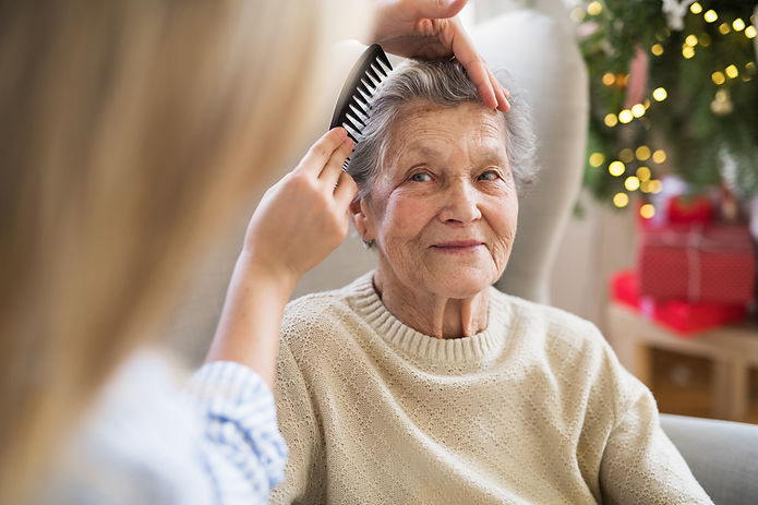 A health visitor combing hair of senior