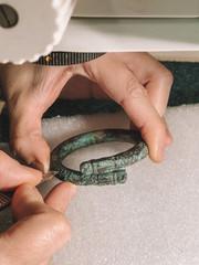 Nettoyage mécanique sous binoculaire d'un bracelet zoomorphe porté par un enfant à l'Âge du Fer