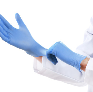 Doctor putting on sterile gloves isolate