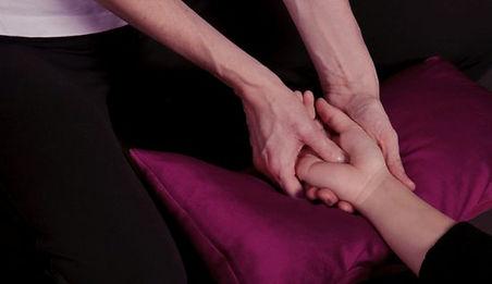 Au cours d'une séance de Shiatsu, Fleur Szabo réalise un point de pression au creux de la main d'une jeune femme
