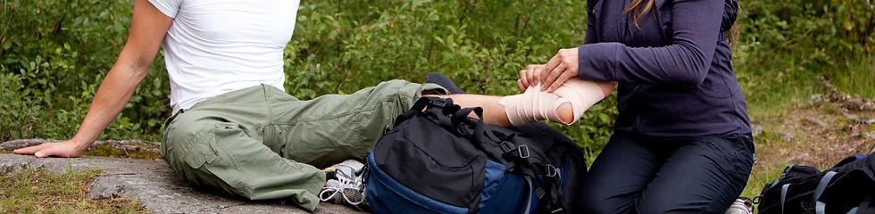 L'image montre une jeune femme qui pose une bande médicale à un homme dans une forêt