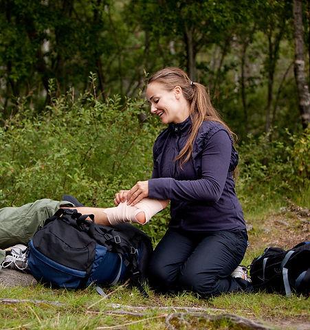 la photo montre une femme pratiquant le secourisme en milieux isolé. Elle pose une bande a la cheville d'un homme