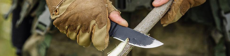 la photo montre les mains d'un homme coupant une branche avec un couteau pour préparer un bivouac