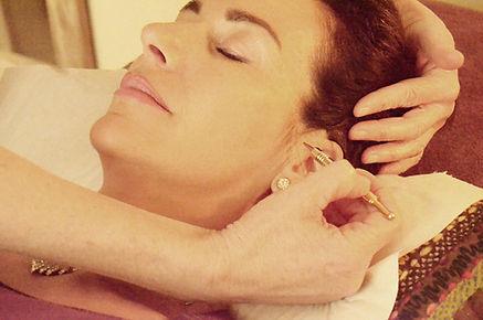 Maryse Théau laurent pratique la reflexologie faciale sur une patiente à l'aide d'un petit outil