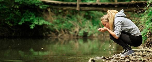 L'image montre une jeune femme buvant l'eau d'une rivière