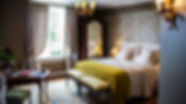 "The guestroom ""la vie est belle"". A king size bed, a desk, and large windows with view on the garden"