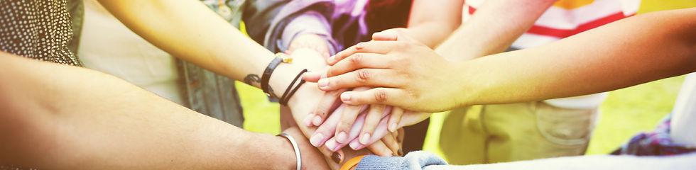 L'image montre des mains qui se posent les unes sur les autres en formant le symbole de l'équipe
