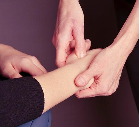 On voit les mains de Fleur Zsabo qui pratique un point de pression sur la main d'une jeune femme lors d'un amma
