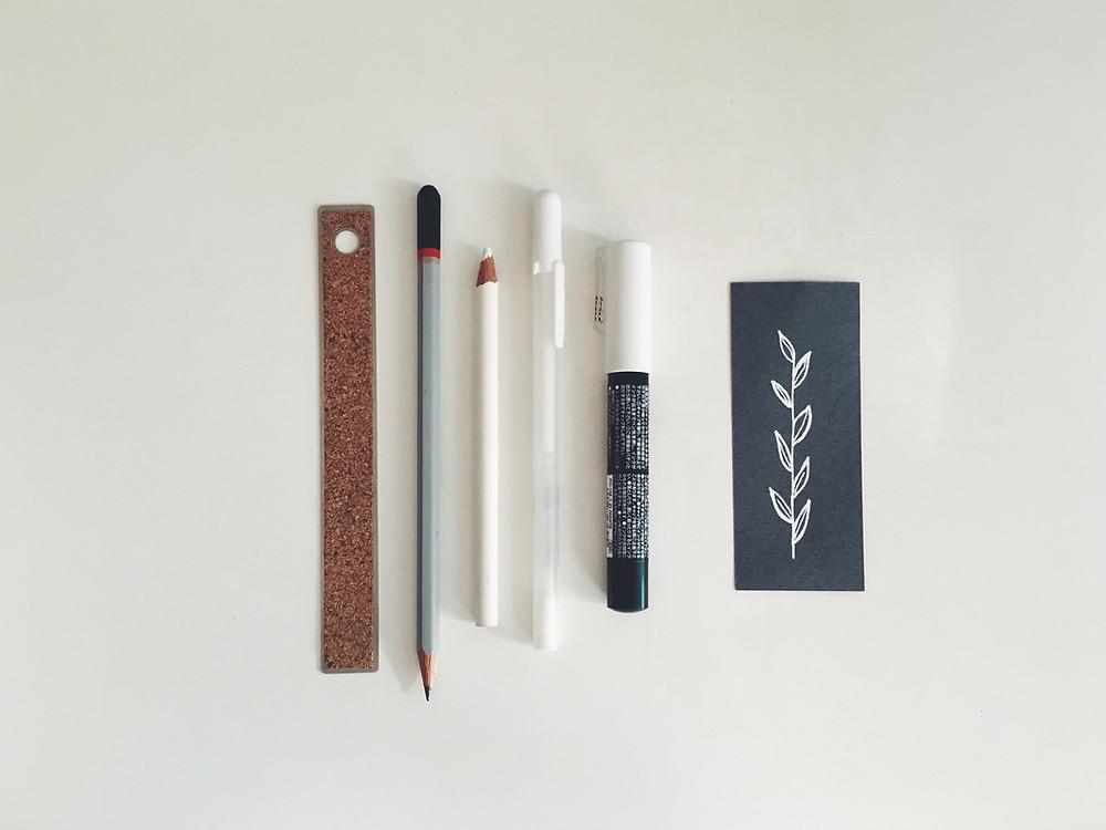 Alinhados verticalmente, da esquerda para a direita: uma régua, um lápis grafite, um lápis branco, uma caneta gel branca, uma caneta grossa branca e um pequeno pedaço de papel com folhas desenhadas em branco
